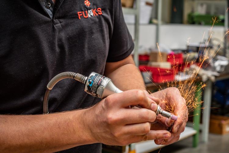 Mitarbeiter schleift ein Stück Metall, dadurch entsteht Funkenflug